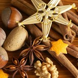 Close-up of spices, nuts and Christmas straw decoration