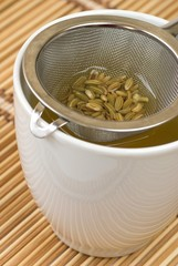 Fennel tee and seeds in a sieve