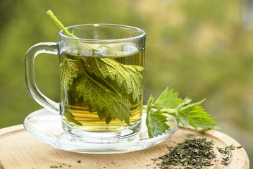 Nettle tea in glass, fresh and dry nettle.