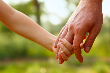 father's hand lead his child son in summer forest nature outdoor