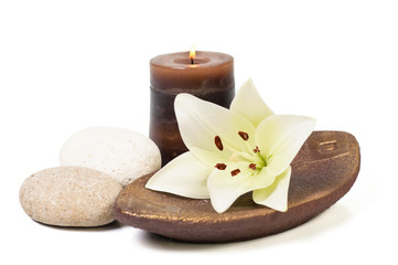 spa decoration with stones, candle and lily on a wooden plate