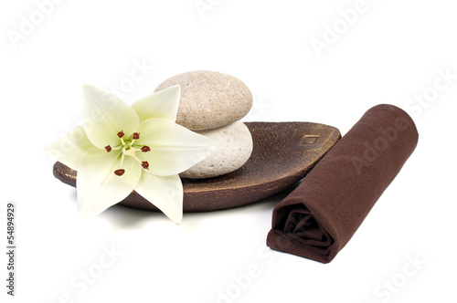 spa decoration with stones and lily on a wooden plate