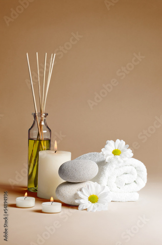 spa decoration with flowers, stones, candles and massage oil