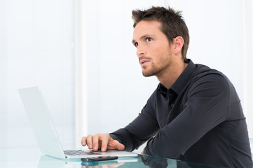 Pensive Businessman Working On Laptop