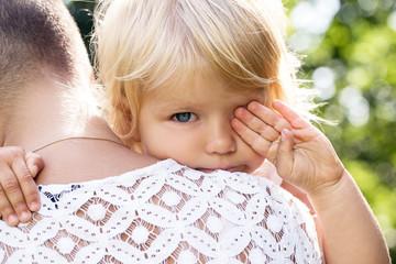 Sad little girl on her mothers' hands