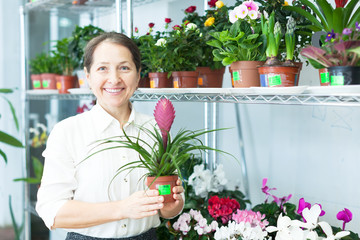 Happy mature woman with Tillandsia plant