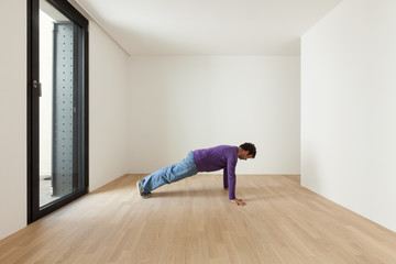 man doing gymnastics in a empty room, interior house