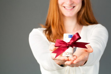 Happy woman giving money as a gift