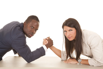 business man and woman arm wrestle serious looking