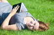 Beautiful woman laying back on green grass with book in hands