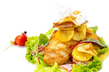 salad with chicken and potatoes on a white plate in a restaurant