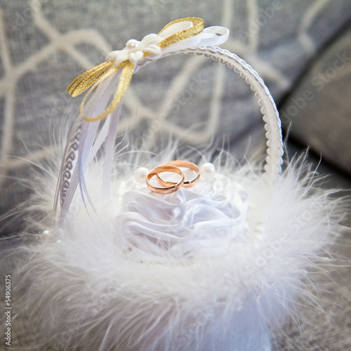 Wedding rings in a white fluffy basket