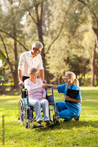 female doctor greeting recovering senior patient in wheelchair