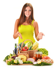 Young woman with assorted grocery products isolated on white