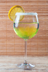 Lemon cocktail in a glass on wooden background