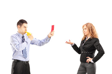 Young businessman blowing a wistle and showing a red card