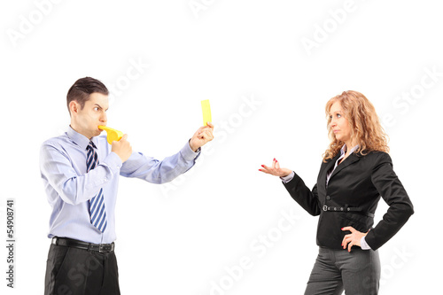 Young businessman blowing a wistle and showing a yellow card to