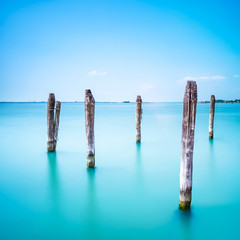Poles and soft water on Venice lagoon. Long exposure.