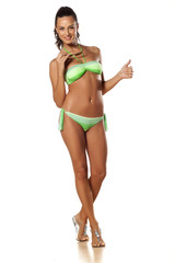 smiling brunette in a swimsuit showing thumbs up