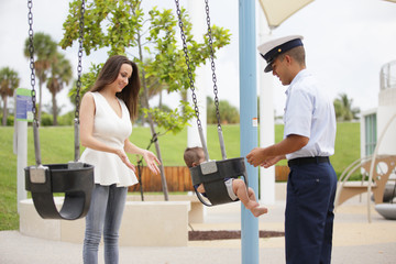 Stock image of parents swinging their child