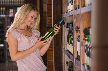 Woman reading the label behind a bottle of wine