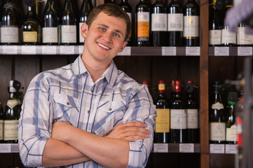 Portrait of confident male with a selection of wines in the back