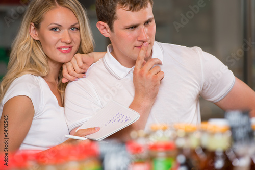 Image of positive couple choosing products in supermarket