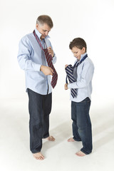 Father is showing his son how to tie a tie