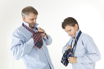 Father is teaching his son to tie a knot on a tie