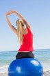 Fit woman sitting on exercise ball looking at sea