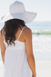 Pretty brunette in white sunhat looking at the sea