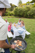 Happy extended family having a barbecue being cooked by father i