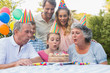 Cheerful extended family watching girl blowing out birthday cand