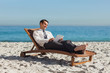 Young businessman relaxing on a deck chair using his tablet