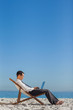 Young businessman on his deck chair using his laptop