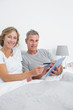 Smiling couple using their tablet pc to buy online