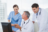 Cheerful doctors and surgeon working together on computer