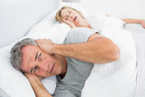 Fototapety Fed up man blocking his ears from noise of wife snoring