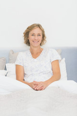 Blonde happy woman sitting in bed smiling at camera