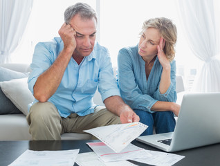 Worried couple using their laptop to pay their bills