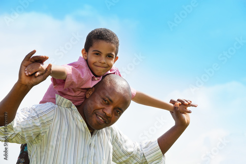 Black boy riding father's shoulders