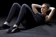 fit woman doing situps on a black background