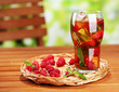 Iced tea with raspberries and mint on wooden table, outdoors