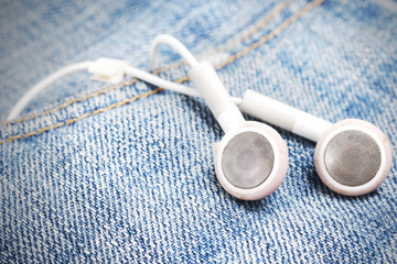white earphone on jeans background