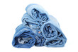 Stack of rolled  blue jeans on white background