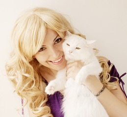 Beautiful young woman holding white Persian cat