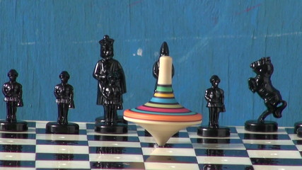 black chess and colorful  wooden toy whirligig on chessboard