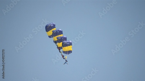 skydivers with open parachutes in formation