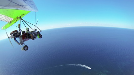 Aerial: Motorized hang glider flying over sea