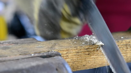 sawing a wood plank close up